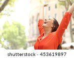 Stock photo excited woman wearing orange blouse raising arms outdoors in the street with buildings in the 453619897