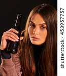 Small photo of Drunk girl drink alcohol from bottle of alcohol on black background. Soccial issue female alcoholism.