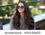 Small photo of Trendy dressed fashionable girl wearing fur coat. Young pretty beautiful woman with long curly hair looking at you.