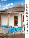 Small photo of Construction of adobe house with thatched roof and plastic windows
