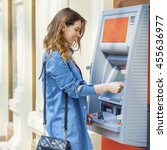 Small photo of Young happy brunette woman withdrawing money from credit card at ATM