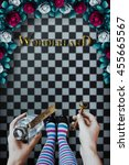 Small photo of Alice in wonderland. Background. A key and a potion in hands against a chess floor, Red roses and white roses