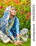 Small photo of Middle age woman in blue sari and Indian adornment sits on lawn in garden