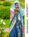 Small photo of Middle age woman in blue sari and Indian adornment holds petals in summer park