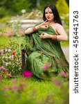Small photo of Brunette pretty woman in sari and Indian adornment poses in garden