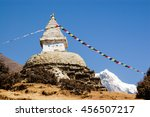 Small photo of Buddhist stupa and colorful prayer flags with blue sky on the acclimatization route at Namche Bazaar in everest region of Nepal.