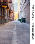 Small photo of Brick alleyway with dumpsters and fire escape and copy space.