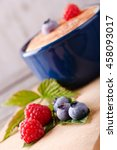 Small photo of Vertical askew photo of few summer berries as red raspberries and big blueberries on green leaves in front of blue bowl full of creamy dessert with cinnamon sugar on surface placed on wooden board.