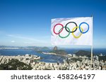 Small photo of RIO DE JANEIRO - FEBRUARY 26, 2016: Olympic flag waves above the city skyline view of Sugarloaf Mountain and Guanabara Bay in celebration of the city hosting the Summer Games.