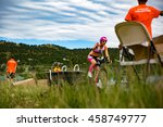 Small photo of Boulder, Colorado, USA - July 24, 2016: A triathlete reaches for a water bottle at a bike aid station during Tri Boulder.