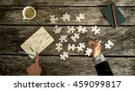 Small photo of Top down view on thumb up and finger pointing to business symbols on notecard beside blank jigsaw puzzle pieces, checkbook and cup over old wooden table.