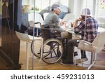Small photo of Full length of handicap businessman discussing with colleague in creative office