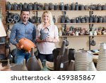 Small photo of Woman and man purchasing clay and ceramic dish-ware in local atelier