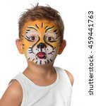Small photo of lovely adorable kid with paintings on his face as a tiger or lion