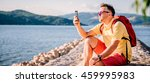 Man in yellow shirt, sunglasses and red backpack sitting on stone dock by the sea and taking pictures with smart phone