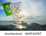 Small photo of RIO DE JANEIRO - FEBRUARY 26, 2016: Olympic and Brazilian flags hang above backlit sunrise skyline view of Sugarloaf Mountain and Guanabara Bay in celebration of the city hosting the Summer Games.