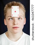 Small photo of Head and Shoulders Close Up of Teenage Boy with Spiked Blond Hair Looking Cross Eyed at Ace of Hearts Playing Card Stuck to Forehead in Studio with Dark Background