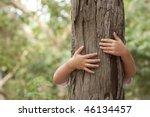 Kid Hans Embracing A Tree Trunk