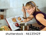 Young beautiful housewife preparing soup. Tries soup and smiles. - stock photo