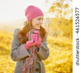 Small photo of Young smiling woman with coffee mug in hands enjoying sunny day in the fall season. Woman wearing fashionable purplish-red hat and gloves on nature yellow background. Outdoor portrait in autumn.