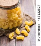 Small photo of Raw macaroni on wooden background