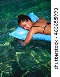 Small photo of Girl sleeping on air bed floating in clear water