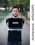 Small photo of Young man writing Adhd on the computer