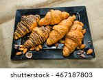 Small photo of Closeup Croissant on a wide variety of dishes. together chocolate and almonds. Focus on Croissant. The background is blurred out of focus at some point.