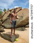 Small photo of Young guy posing with a coconut on the coast the Indian Ocean in Sri Lanka. Ambalangoda beach 29 May 2016