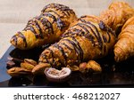 Small photo of Closeup Croissants on a wooden plate. chocolate and almonds. Focus on Croissant. The background is blurred out of focus at some point.