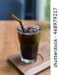 Small photo of Iced Americano black coffee on a wooden table. shallow depth of field