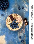 Small photo of Gluten free amaranth and quinoa porridge breakfast bowl with blueberries and chocolate over vintage blue background. Top view, overhead, flat lay. Copy space