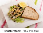 Small photo of dried stint on salad with garlic and parsley, a slice of bread and lemon on a plate