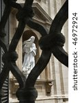 Small photo of Statue of Saint Teresa of Avila seen through opening in iron fence. Vertical shot.