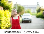 Small photo of Beautiful blonde woman in a red dress pensively looks afar. Car the background.