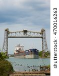 Small photo of St. Catharines, Ontario, Canada - August 15, 2016: The Algoma Transport self-discharging bulk carrier passing under the Glendale Road lift bridge while navigating south up the Welland Canal