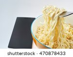 Small photo of Instant noodle and mobile phone technology concepts affect health.