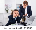 Small photo of Sad dreary subordinate woman being accused to making mistake by man colleague in company office