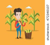 a happy farmer holding a corn... | Shutterstock .eps vector #472340107