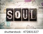"""Small photo of The word """"SOUL"""" written in vintage dirty metal letterpress type on a whitewashed wooden background with ink and paint stains."""