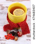 Small photo of Cup of tea with lemon wrapped woolen scarf, warming beverage for flu and cold, autumnal decoration of chestnut, rowan and alder cone