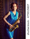 Small photo of Beautiful actress with saxophone standing by a vintage wallpaper. Professional musician.