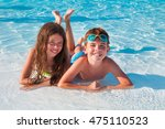 two kids lying on the beach | Shutterstock . vector #475110523