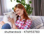 Girl With Samoyed Dog On Couch