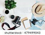 Small photo of Beautiful hipster flatlay with hat, dslr camera, lens, coffee, map, flower, notebook and binocular. Working space surface top view. Creative work table for photographer, traveller, blogger