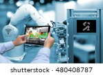 Small photo of Industry 4.0 concept .Man hand holding tablet with Augmented reality screen software and blue tone of automate wireless Robot arm in smart factory background
