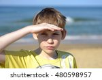 Small photo of Portrait of the boy of the teenager looking afar on the seashore