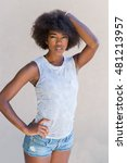 Small photo of Beautiful afro american lady striking pose against background
