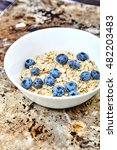 Small photo of Raw oat flakes topped fresh blueberries in white bowl. Organic food on metal, grunge background. Dietary, tasty ingredients for delicious and healthy breakfast Vitamin and energy booster for whole day