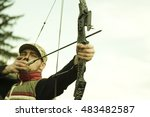 Small photo of A young archer pulls on the bow string, taking aim at his target.